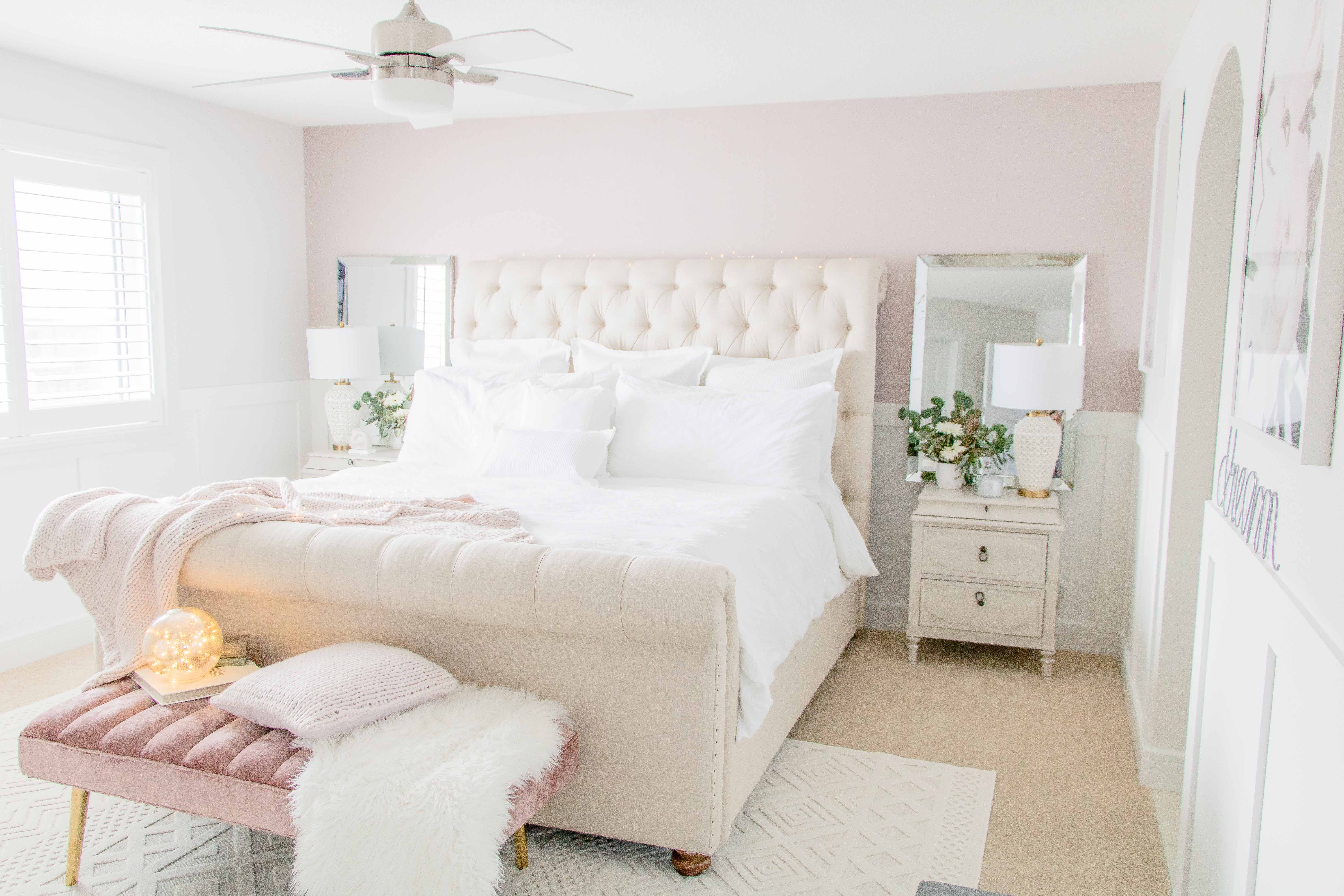 Bedroom with pink walls and white linen on the bed