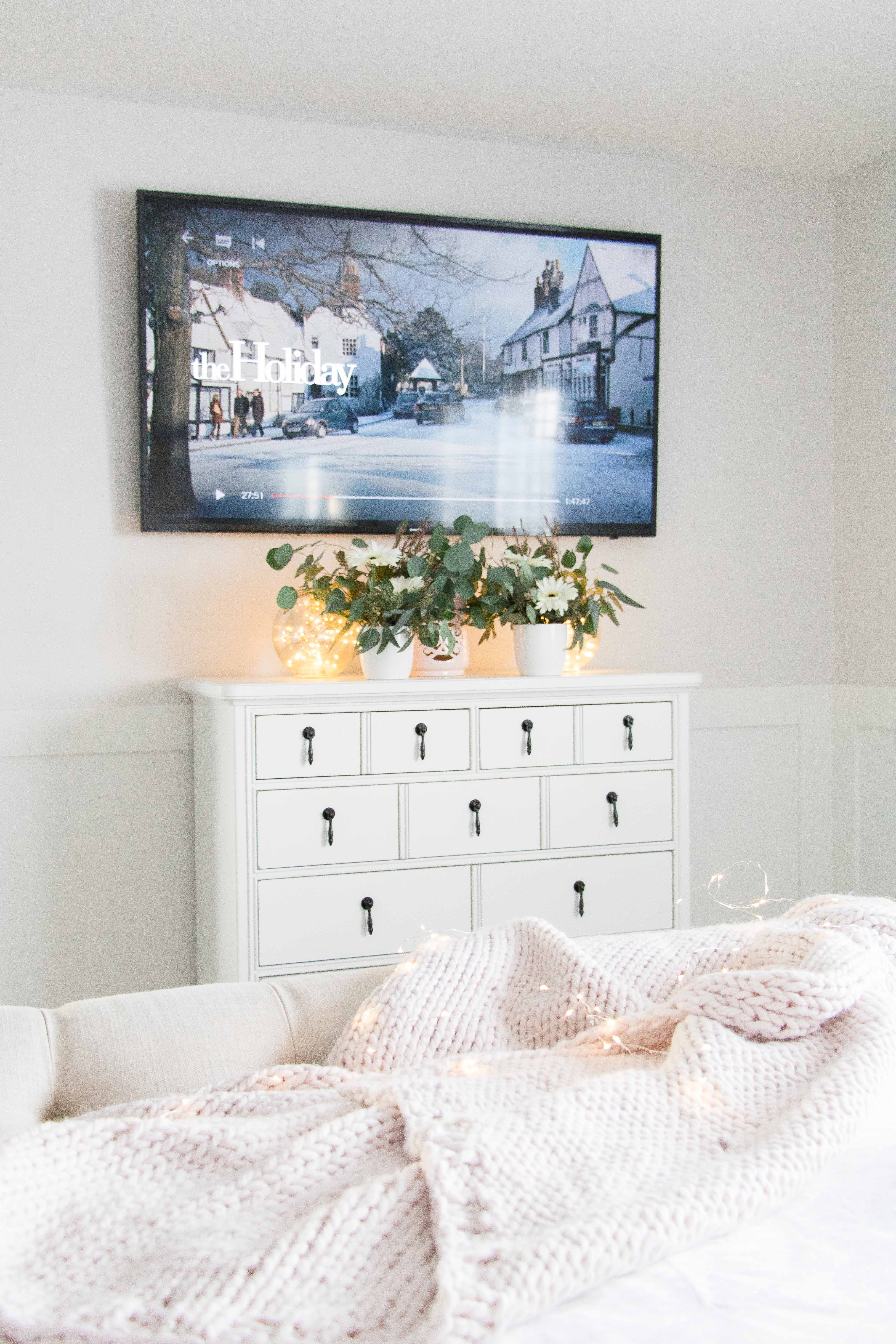 White bedroom dresser with TV above it