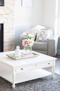 White coffee table with a vase of pink flowers on top