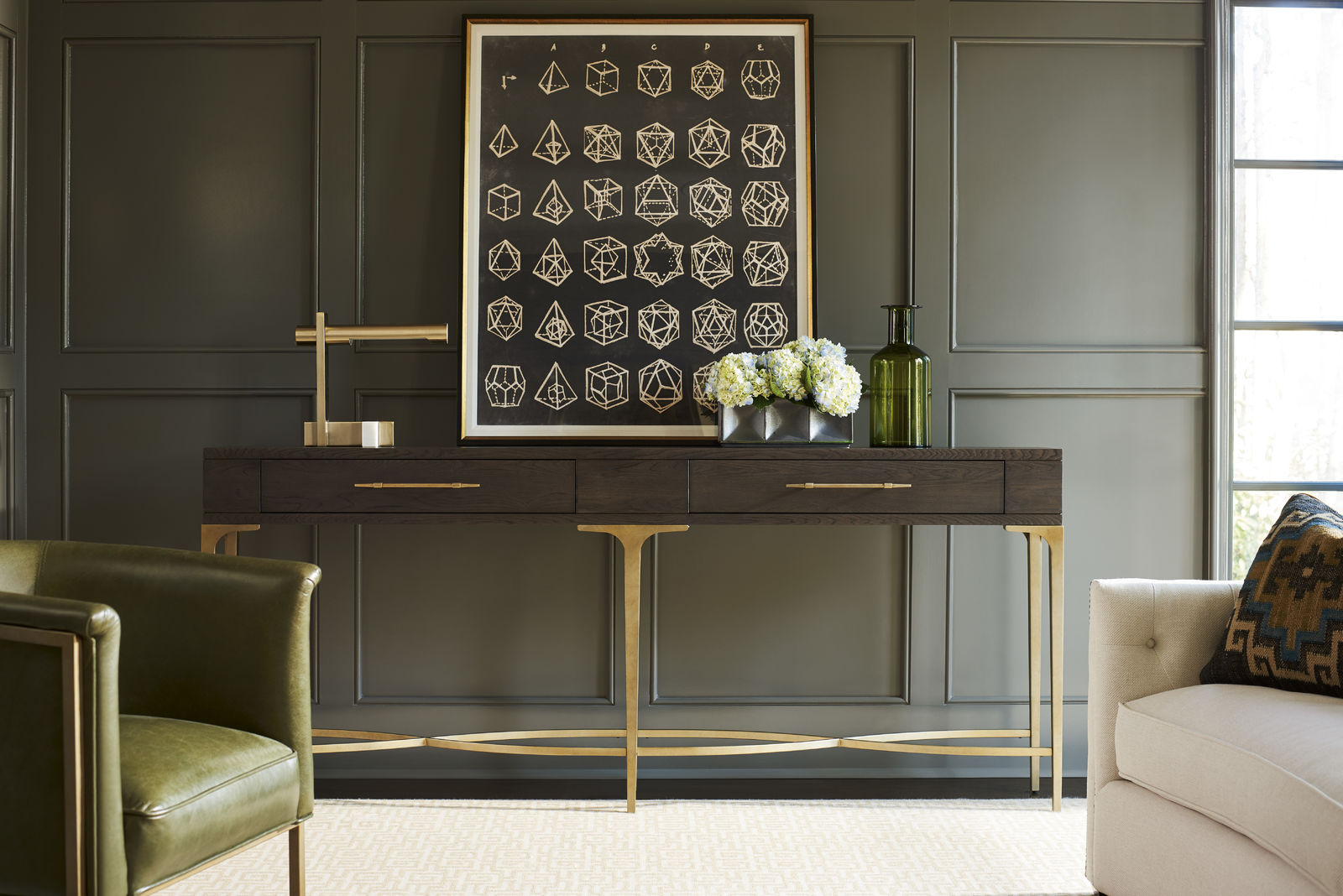 A dark brown and gold console table with a large piece of art resting on top of it