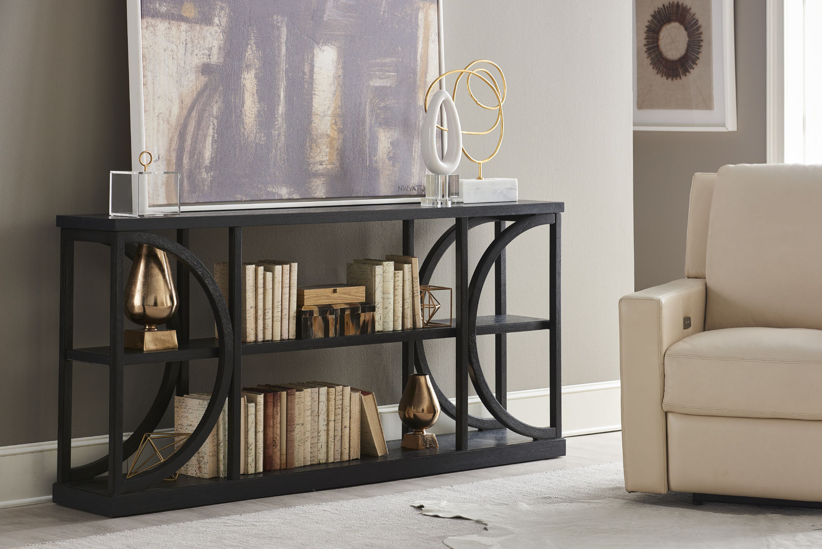 Black console table with books stored inside it and a piece of art resting on top of it