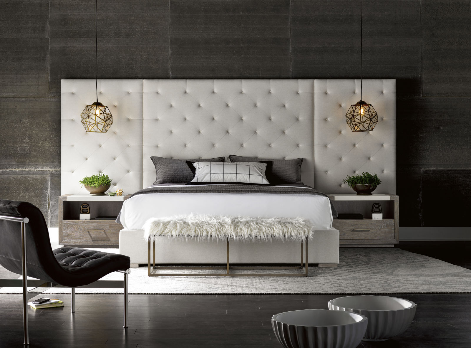 White upholstered bed with gold pendant lights, nightstands and a bench
