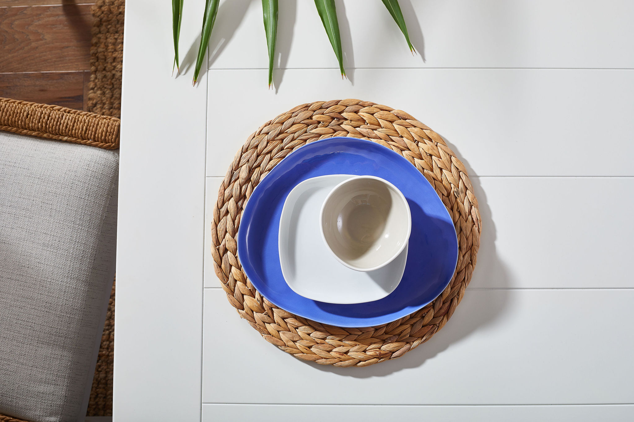 Woven placemat with a blue plate, white side plate and white bowl on top