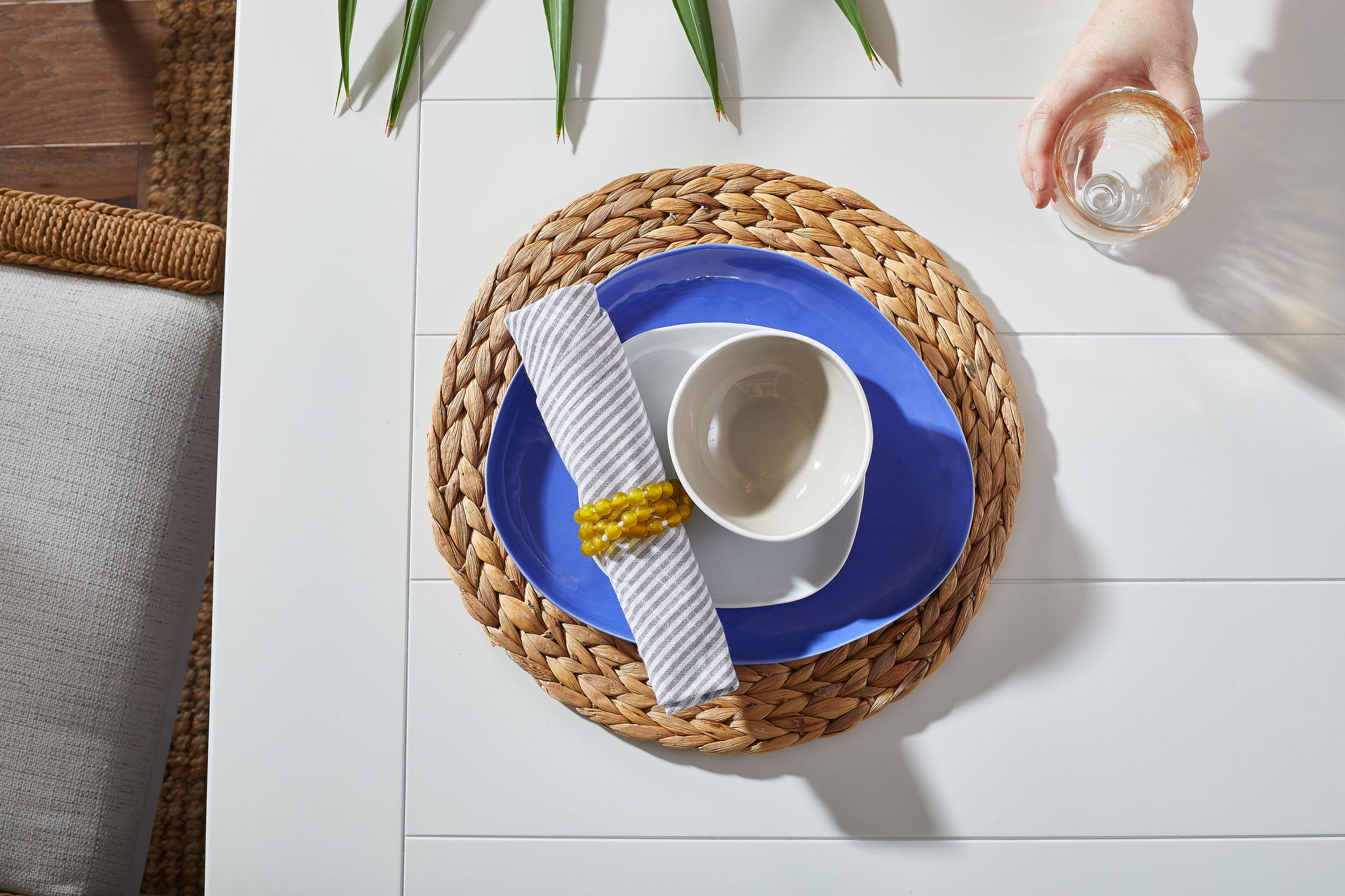 Place setting with a woven placemat, blue base plate, white bowls and a clear glass.