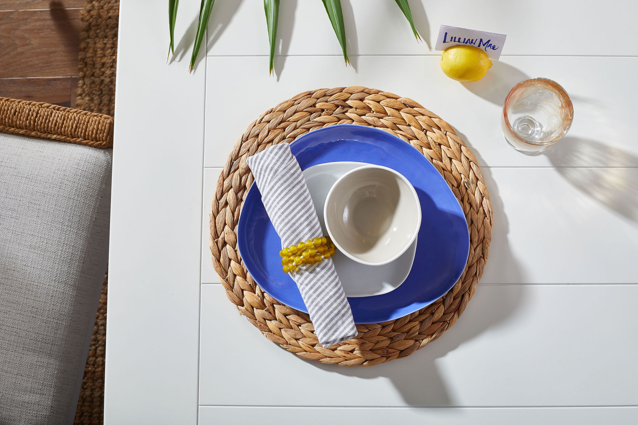 Place setting with a woven placemat, blue base plate, white bowls, a clear glass and a lemon with a nametag in it.