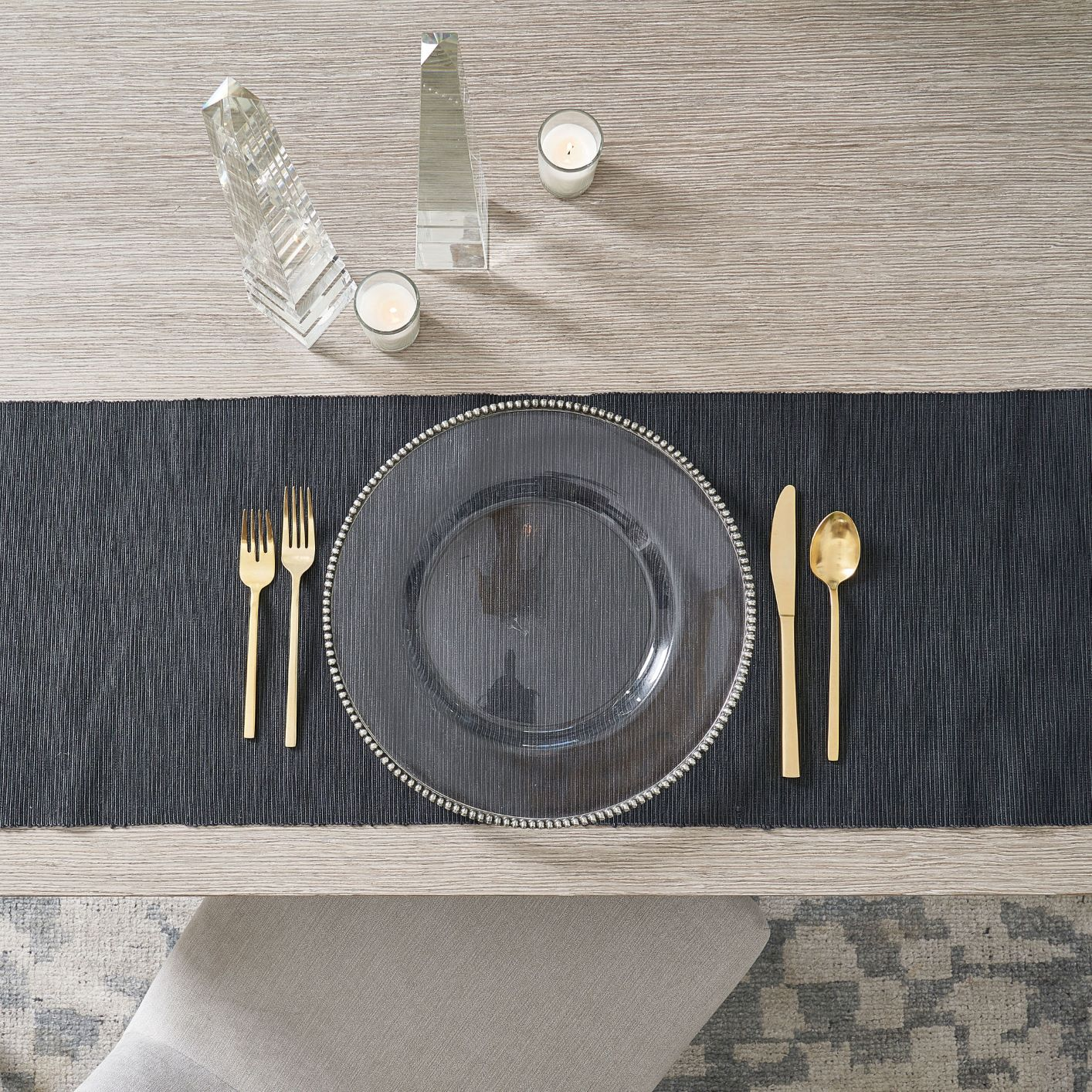 table with black tablecloth, plate and gold flatware