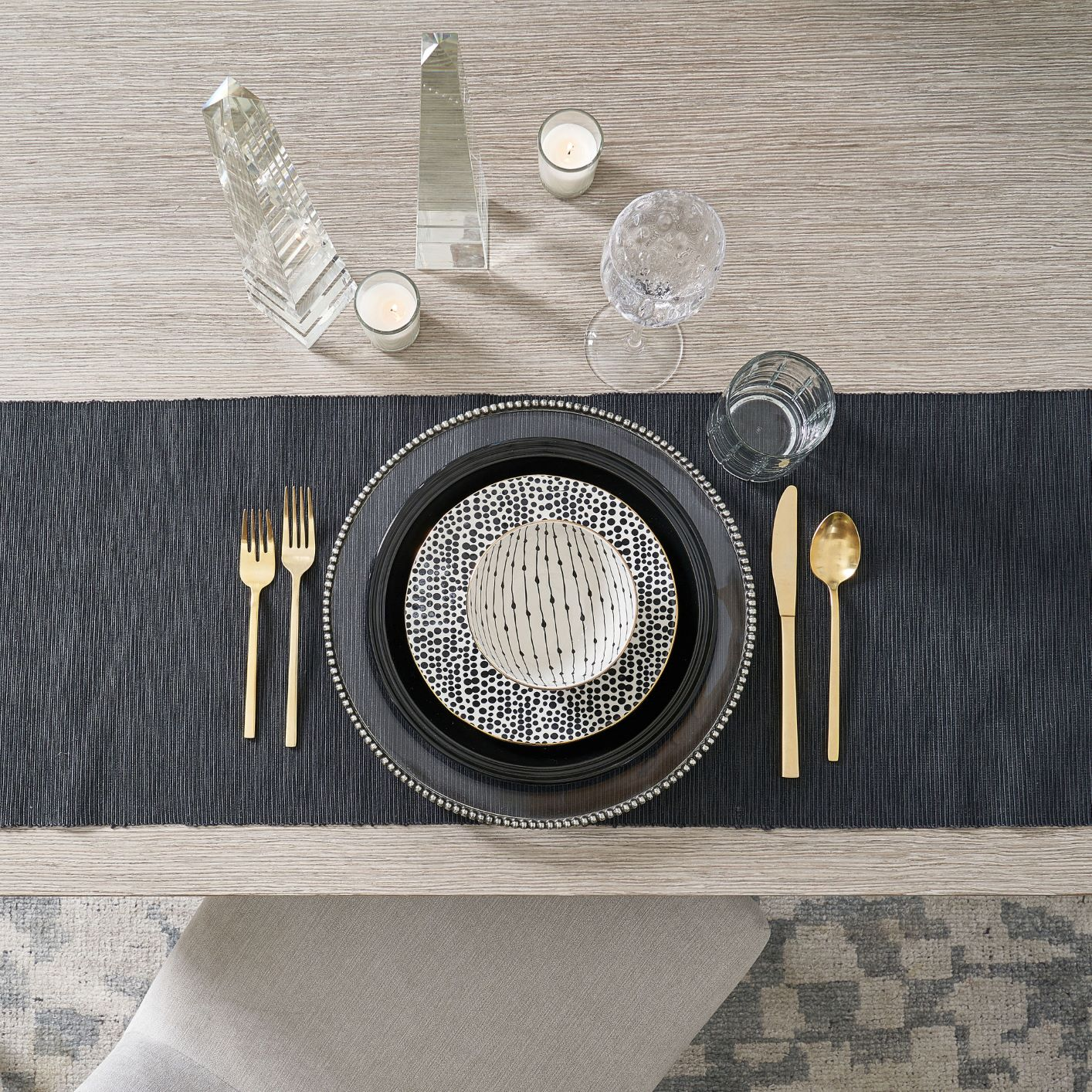 table with black tablecloth, plate, gold flatware, glasses, and patterned bowls