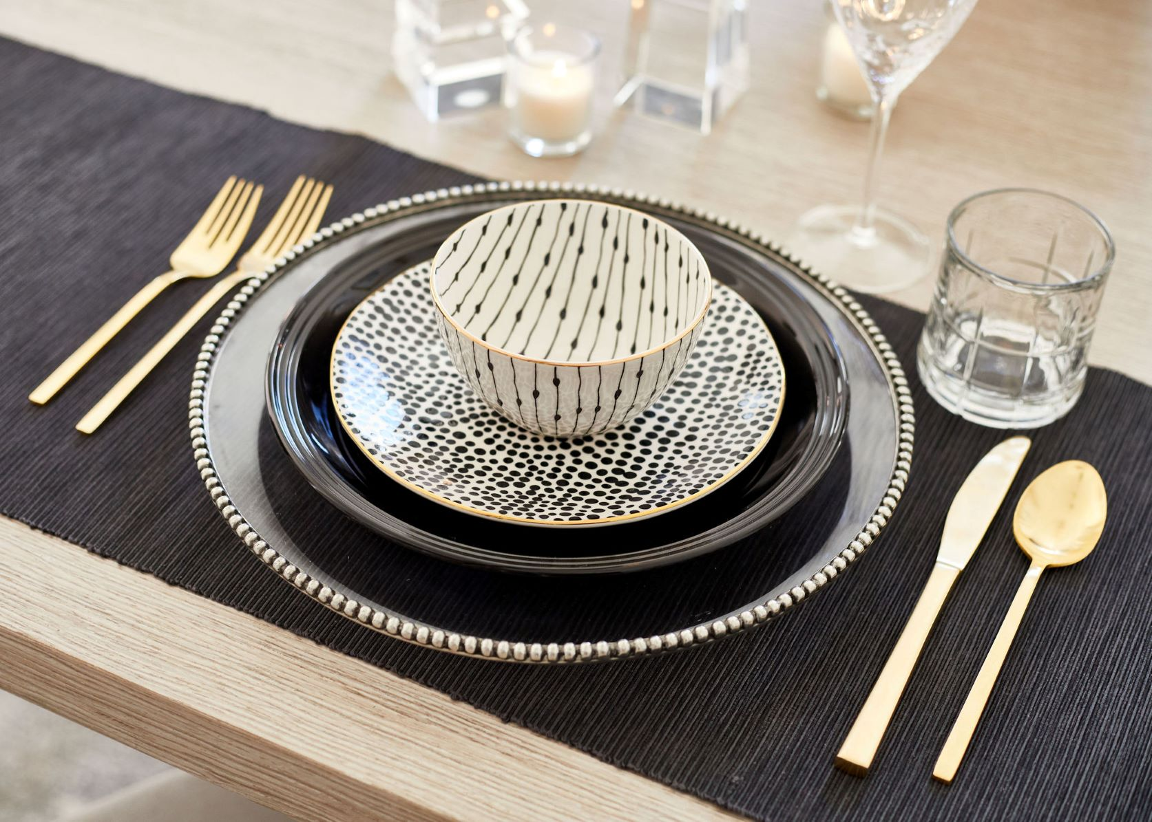 table with black tablecloth, plate, gold flatware, and patterned bowls